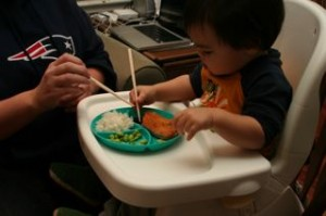 Trying to show him how his chopsticks work.
